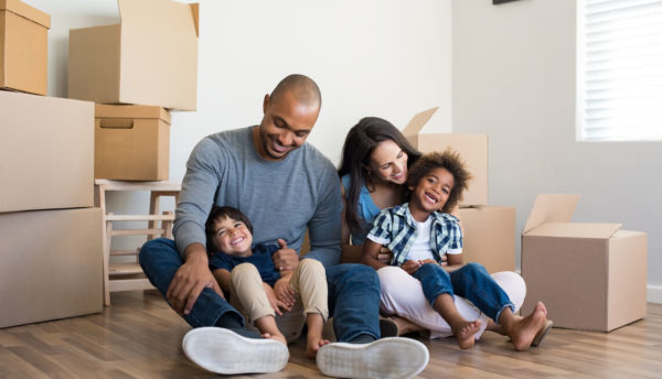 A family with two kids sitting on the floor among moving boxes