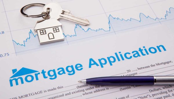 Mortgage application close up with a pen and house key in the frame