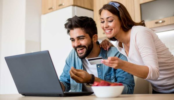 couple smiling while looking at a laptop with a credit card in hand