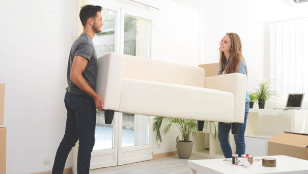 man and woman moving white couch