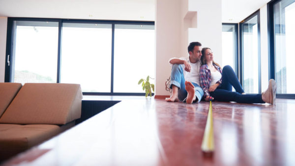 Couple sitting on the floor of their home with a measuring tape stretched out in front of them