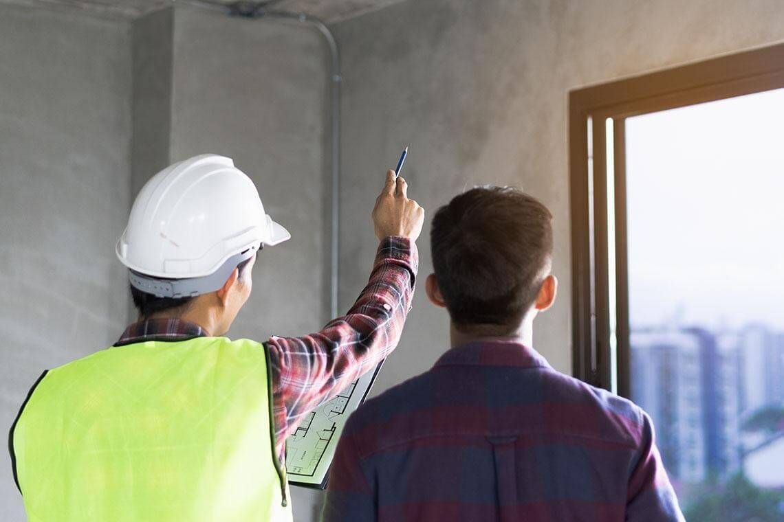 A man in a hardhat and yellow vest holding a floor plan while pointing something out to another man