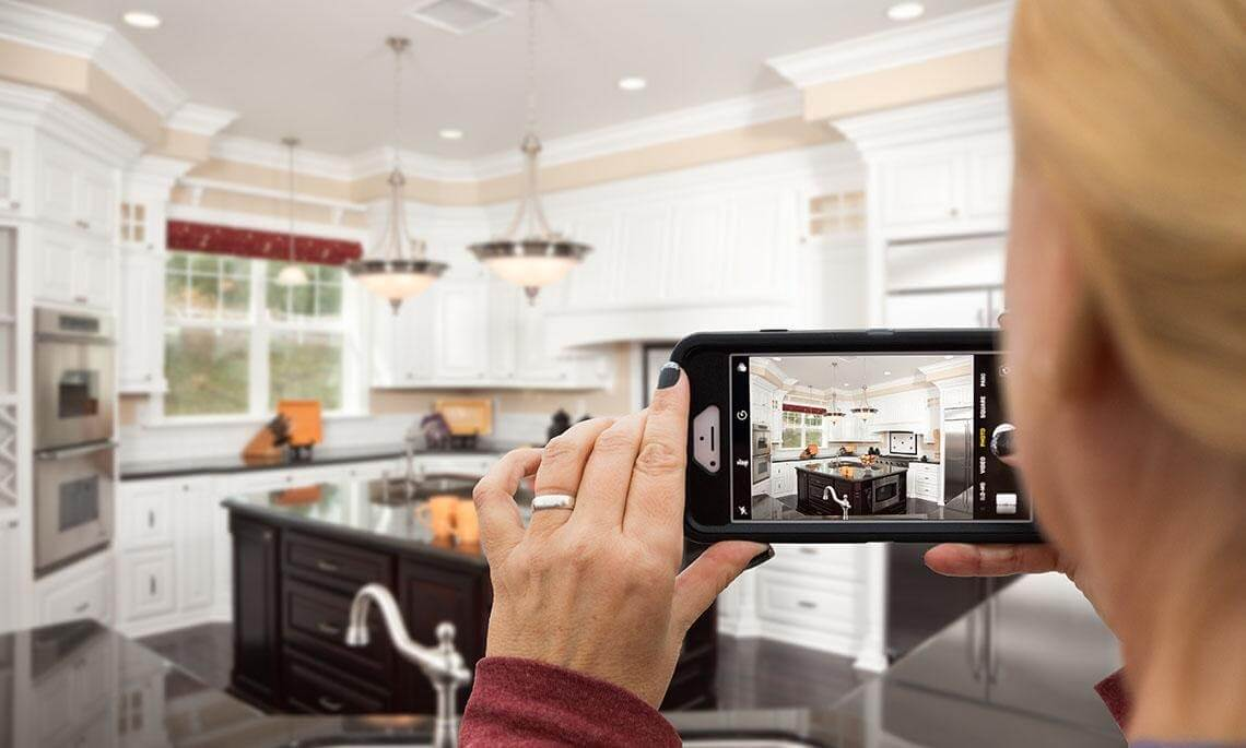 Someone taking a picture of a kitchen with a mobile phone