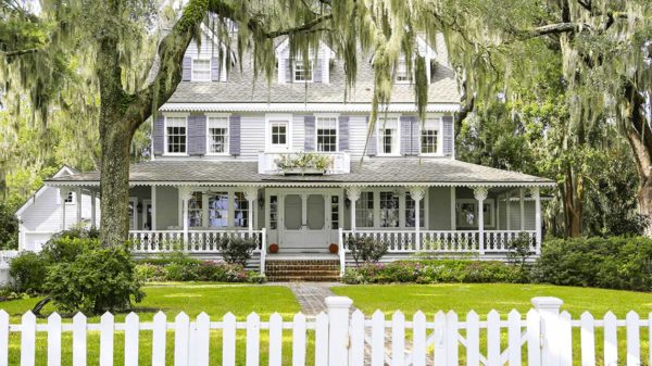 House with a porch, lawn, and picket fence