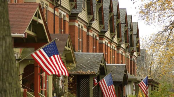 American flags flowing outside brick town homes