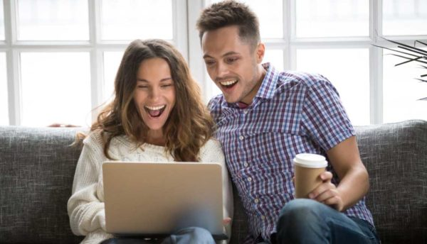 couple looking excitedly at a laptop