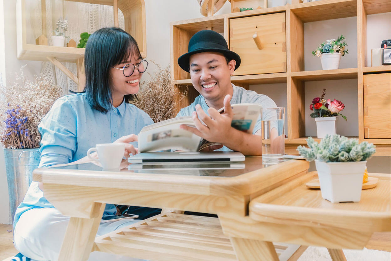 Couple looking through a book seated around a coffee table