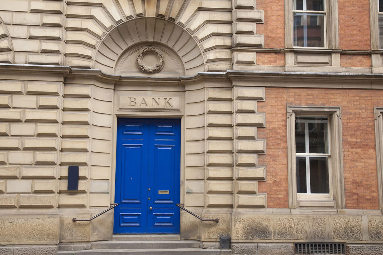 From street photo of the front of the entryway of an old back with a large archway brick building and blue double-doors