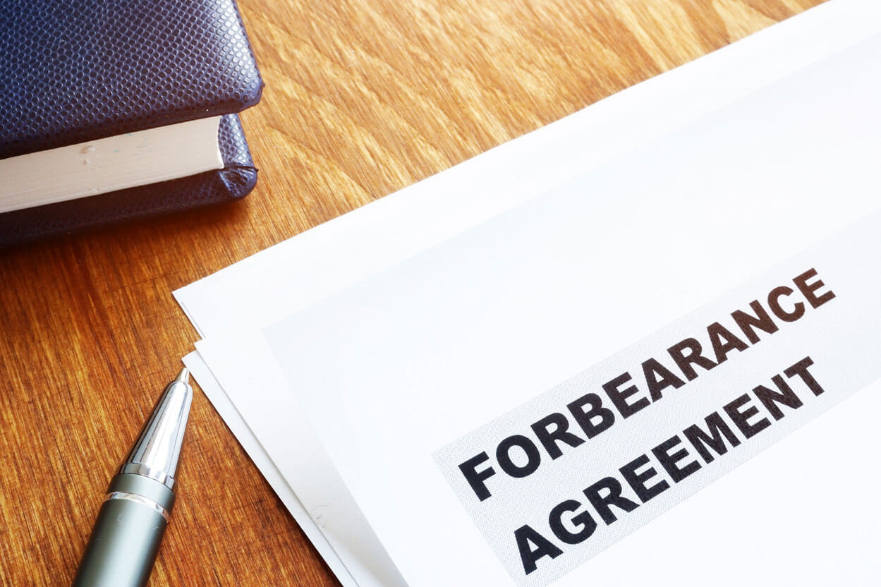 Paperwork on a desk with the title Forbearance Agreement