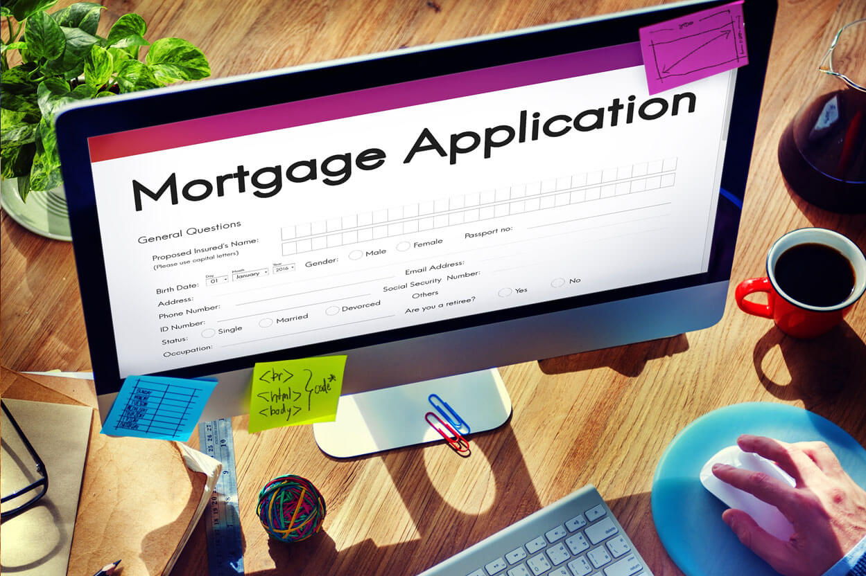 Man workiing on a computer with a mortgage application on the monitor