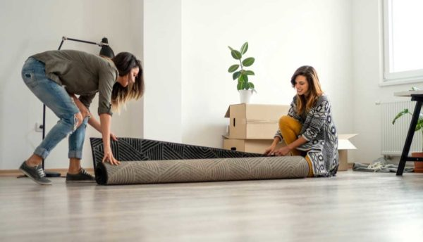 two people unrolling a rug after moving