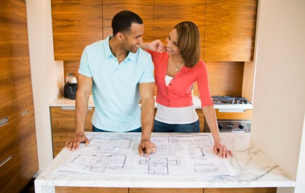 Husband and wife looking at architectural plans for their home
