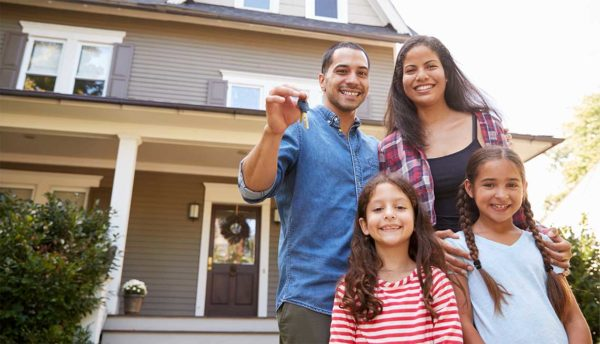Husband and wife next to their 2 daughters holding keys to their home