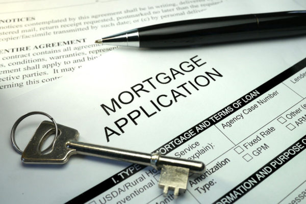 Close up of a mortgage application with a pen and key resting on top