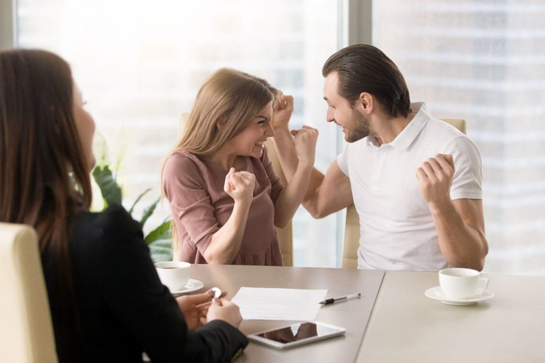 Excited couple pumping fists at a desk in front of a business woman