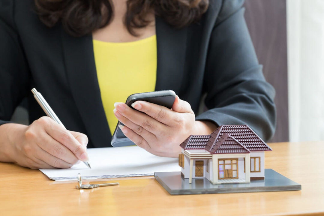Woman doing paperwork while looking at something from her phone. A key and small model home site on the table.