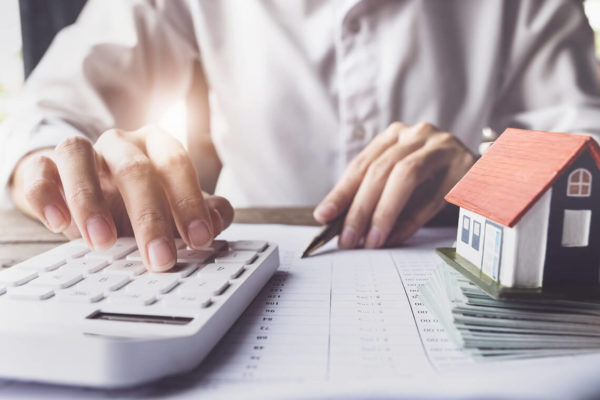 Person using a calculator for refinancing