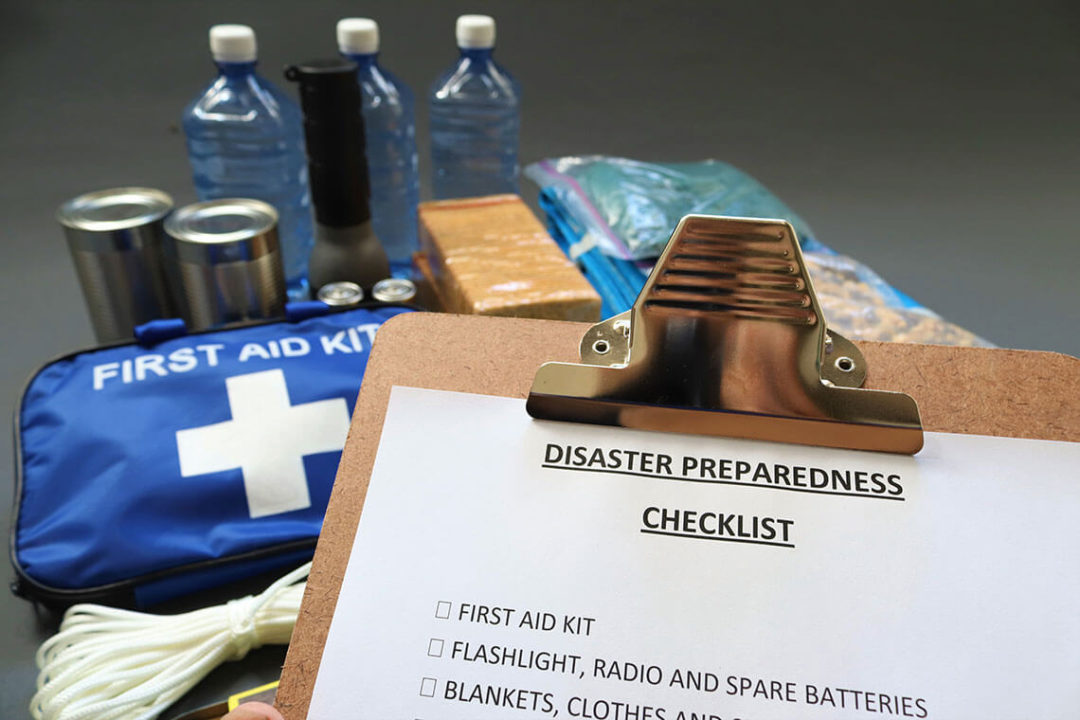 First aid supplies and bottled water in front of a clipboard with a paper titled Disaster Preparedness Checklist