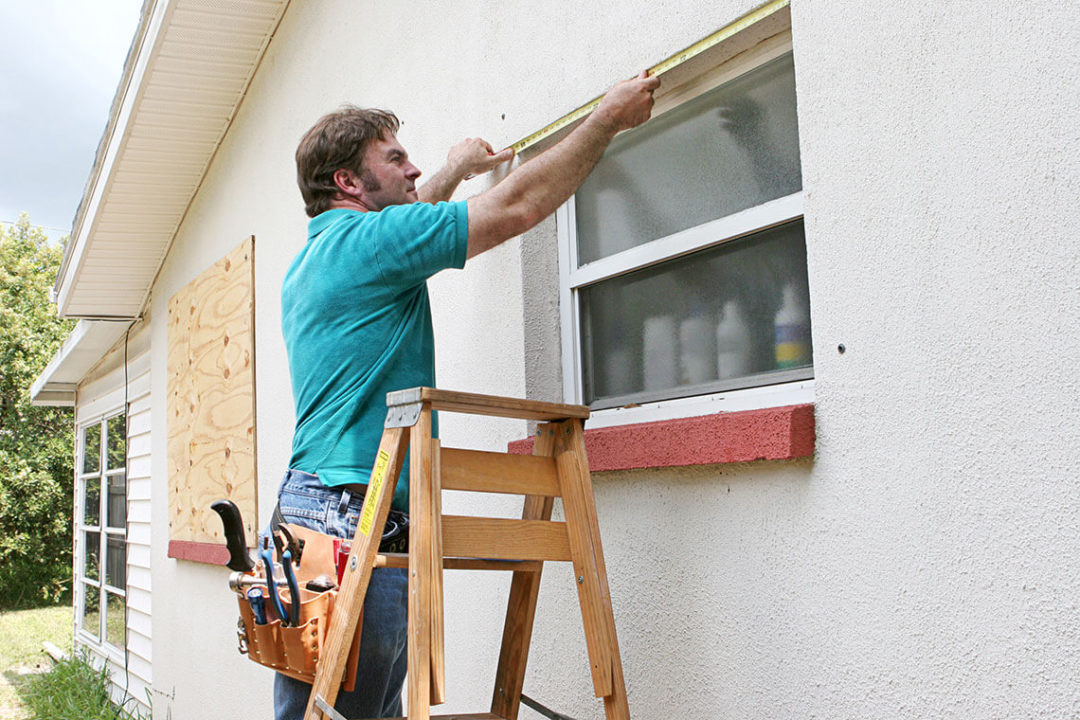 Man on a stepladder measuring a window, with a boarded up window behind him