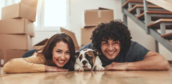husband and wife just moving inot home cuddling with dog