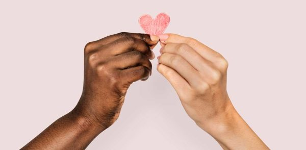 2 hands holding a heart for giving back