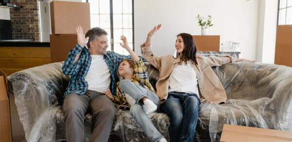 family sitting on a couch adn high fiving